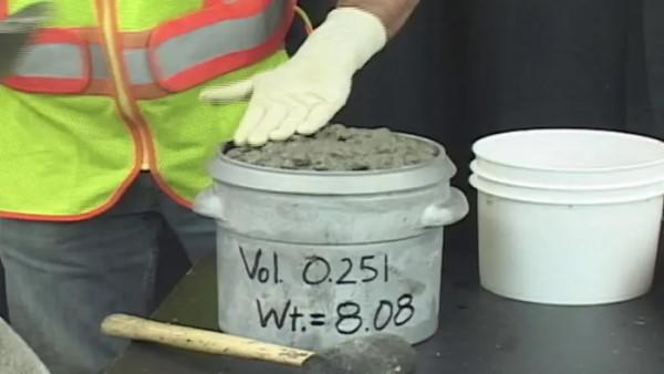 صاف کردن سطح بتن درون محفظه برای تعیین چگالی بتن
